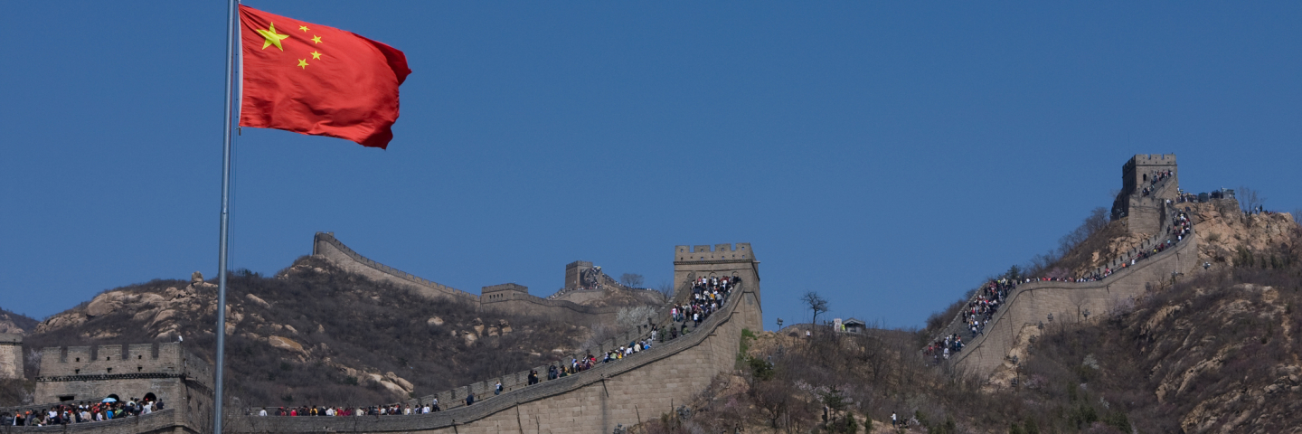 A photograph of the Great Wall China with the Chinese flag waving in the wind.