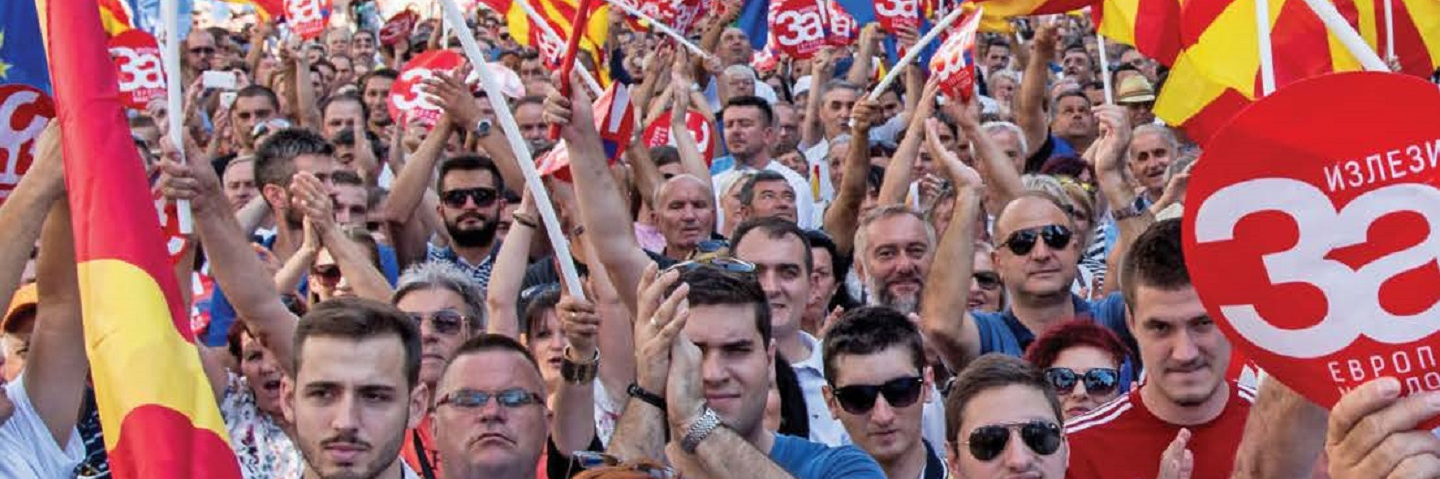 "People in Skopje wave the Macedonian and European Union flags at a rally before a referendum in 2018 on whether to change the country's name to ""Republic of North Macedonia."""