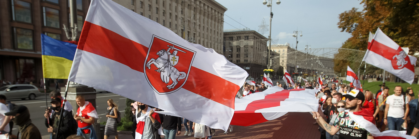 People hold the historical white-red-white flags of Belarus during a rally of solidarity with Belarusian protests in Kyiv, Ukraine on 04 October 2020.
