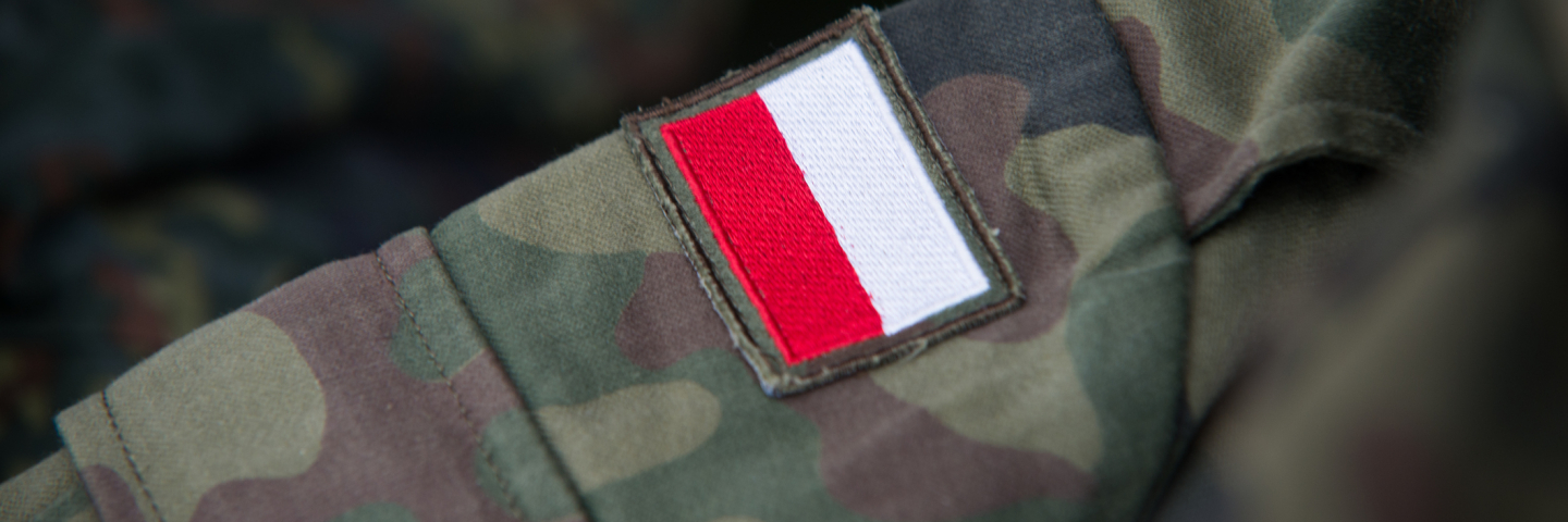Red and white patch on military fatigues designating the solider as Polish.
