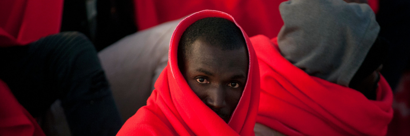 A migrant keeps warm in a Red Cross blanket after arriving aboard a coast guard boat at Malaga's harbour on December 7, 2017, after an inflatable boat carrying 47 men, 7 women and 1 child was rescued by the Spanish coast guard off the Spanish coast.
