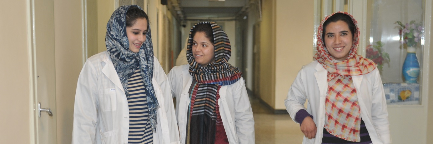 Two female medical interns and a doctor walk the corridors of Kabul National Military Hospital.