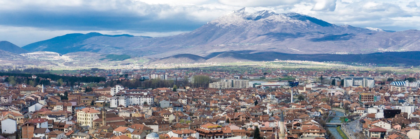 Photo of Kosovo, including city, mountains in the background and a river.