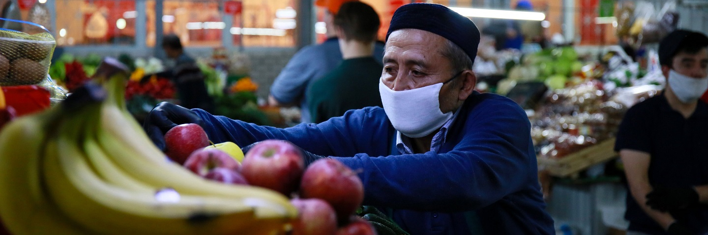 A vendor arranges fruits and vegetables at a market in Almaty on April 25, 2020, amid the coronavirus pandemic.