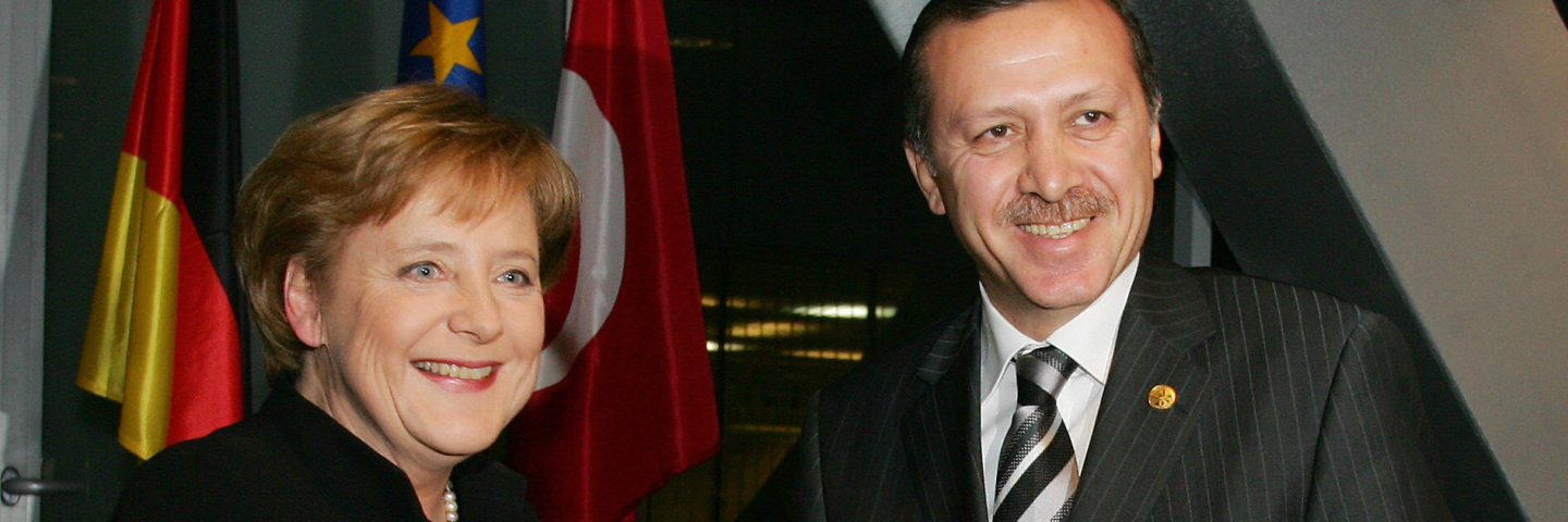 German Chancellor Angela Merkel (L) shakes hands with Turkish Prime Minister Recep Tayyip Erdogan
