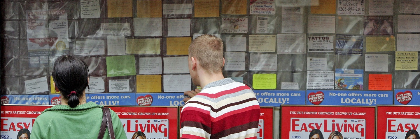 Polish people look at a job message board outside a shop in an area popular with Polish people on May 15, 2006 in west London, England.