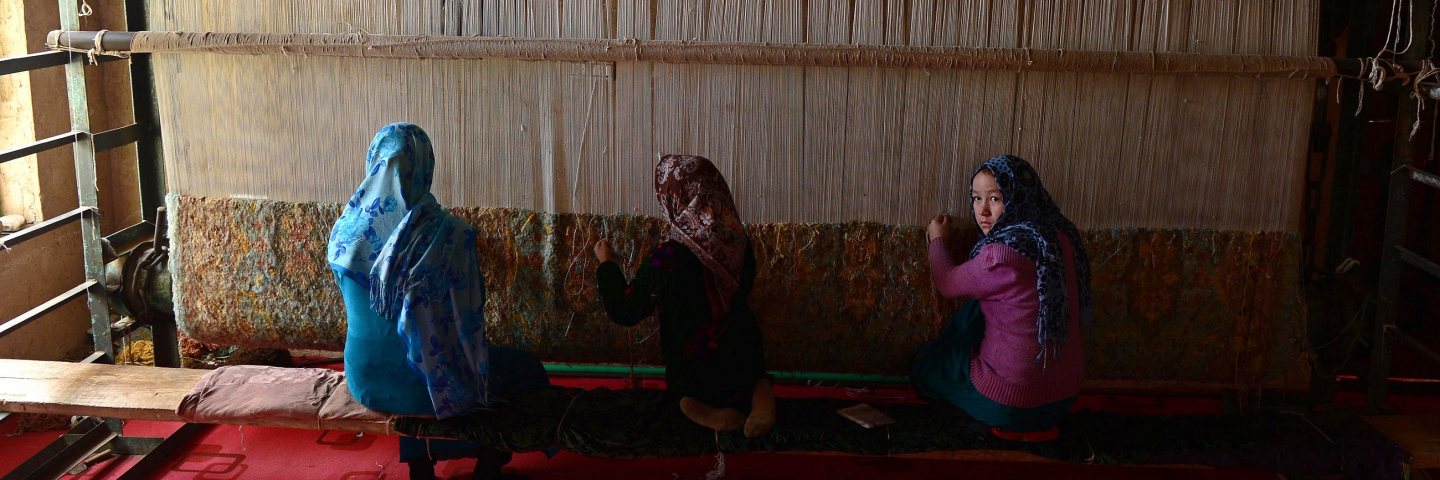 In this photograph taken on December 17, 2014 young Afghan girls weave a carpet at a carpet manufacturer in Herat. Some 42,500 women and their families are involved in the project which aims to provide a means of subsistence and potentially lead to international market access for silk producers in the country.