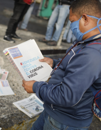 "A man reads a newspaper whose headline reads ""Venezuela united against the Coronavirus"" outside the closed National Transport Terminal on March 17, 2020 in Caracas, Venezuela."