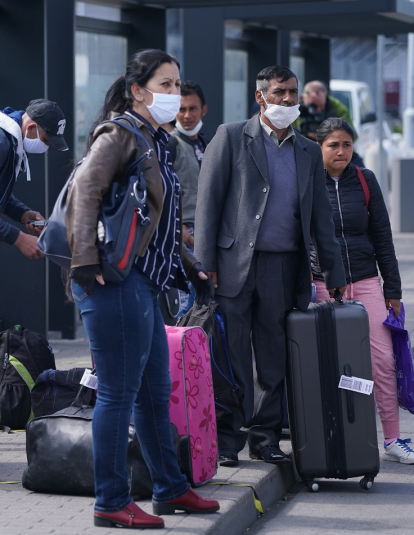 Seasonal workers from Romania board wait to board buses after arriving on a chartered flight at Schoenefeld Airport during the coronavirus crisis on April 09, 2020 in Schoenefeld, Germany.