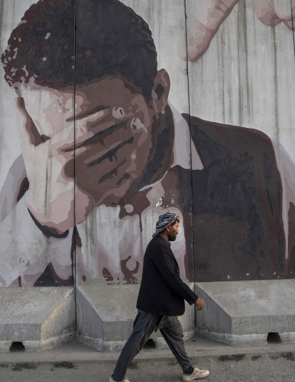 A man walks by a mural painted on a blast wall on September 29, 2019 in Kabul, Afghanistan.