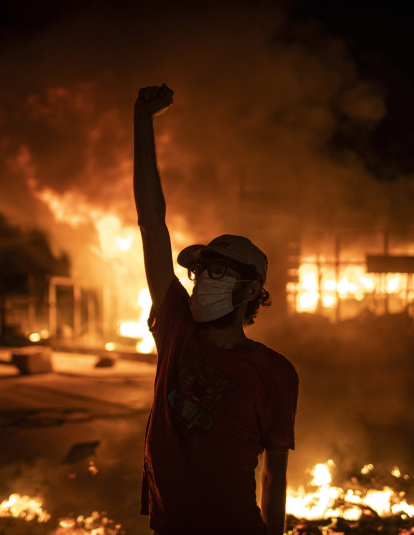 A protester wearing a face mask raises his fist in front of a burning building as large-scale protests resume on June 11, 2020 in Beirut, Lebanon.
