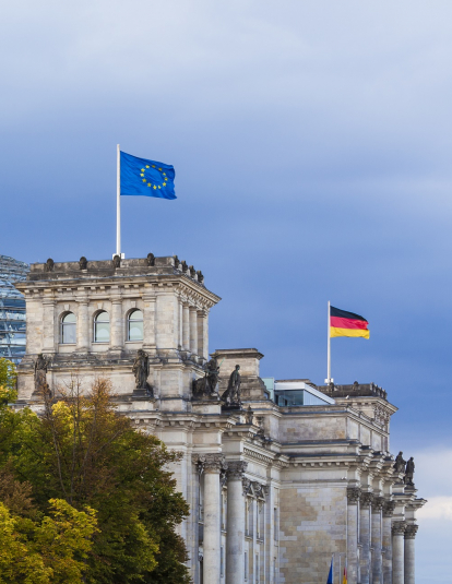 Germany, Berlin, Berlin-Tiergarten, Reichstag building with flags of EU and Germany.
