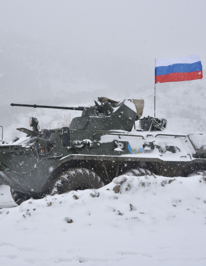 A Russian soldier of the peacekeeping force stand next to an Armored Personnel Carrier (APC) guard a checkpoint on the road to Lachin outside the town of Stepanakert on November 29, 2020, after six weeks of fighting between Armenia and Azerbaijan over the disputed Nagorno-Karabakh region.