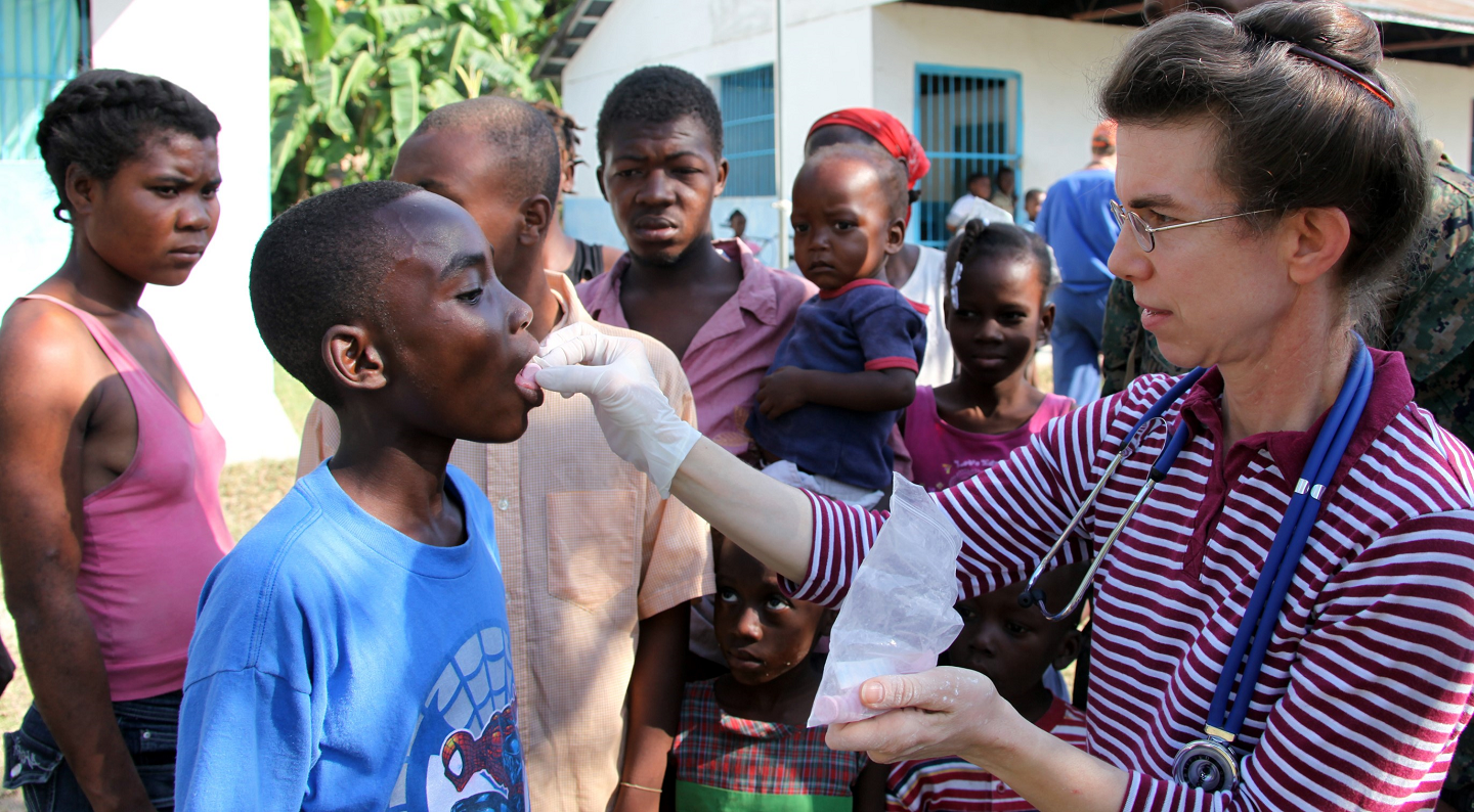 Photo of humanitarian aid worker administering medicine to a Haitian child