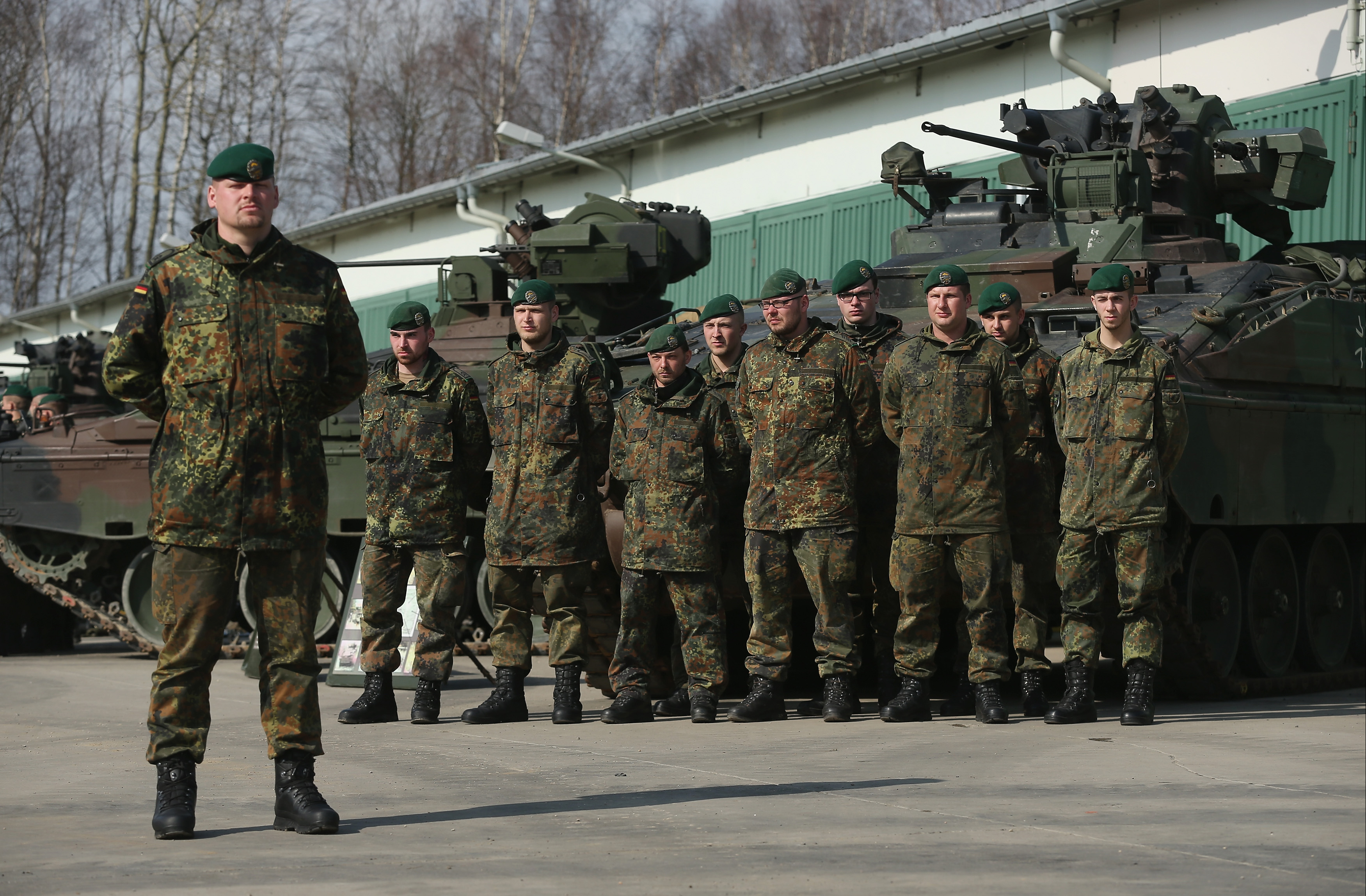 MARIENBERG, GERMANY - MARCH 10: Members of the German Bundeswehr's 371st Armoured Infantry Battalion (Panzergredanadierbataillon 371) stand to attention with Marder light tanks during a media event at the battalion's base on March 10, 2015 in Marienberg, Germany.