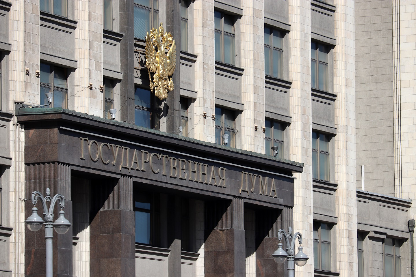 "A photograph of the facade of Russian Parliament building in Moscow with emblem of Russia and inscription ""State Duma""."