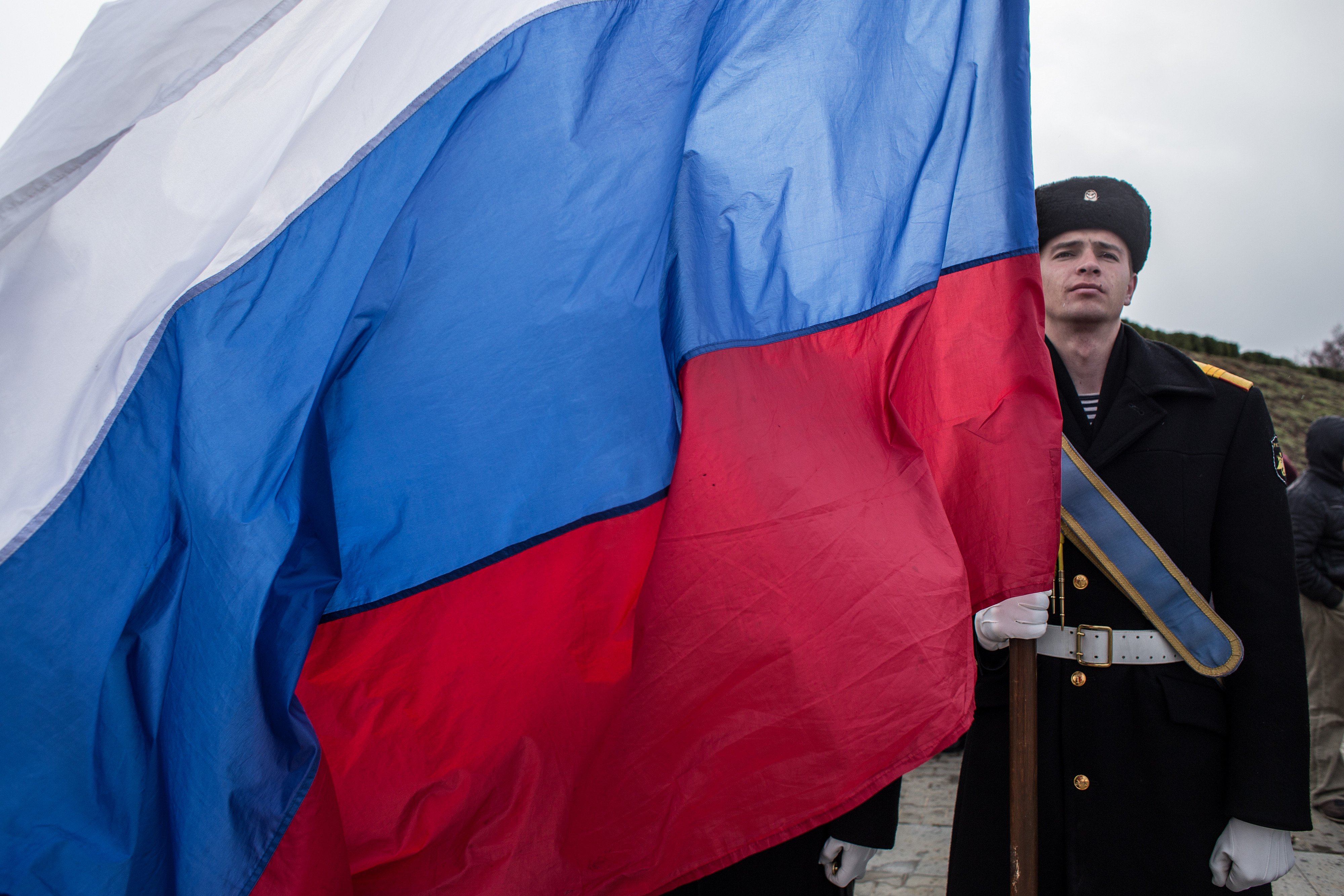 A Navy sailor holds a Russian flag as people celebrate the first anniversary of the signing of the decree on the annexation of the Crimea by the Russian Federation, on March 18, 2015 in Sevastopol, Crimea.