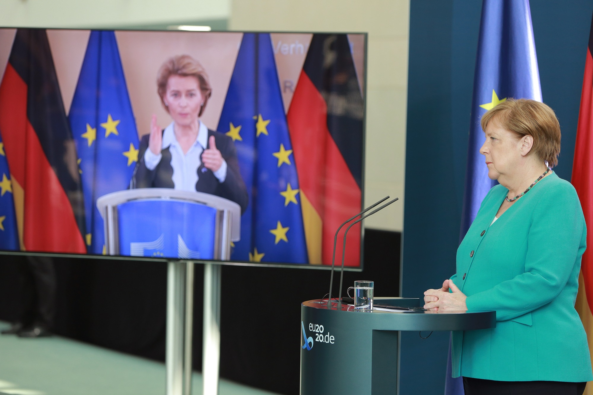 A photograph of  German Chancellor Angela Merkel and European Commission President Ursula von der Leyen (via live video transmission) speak to the media following talks at the Chancellery on July 2, 2020 in Berlin, Germany.