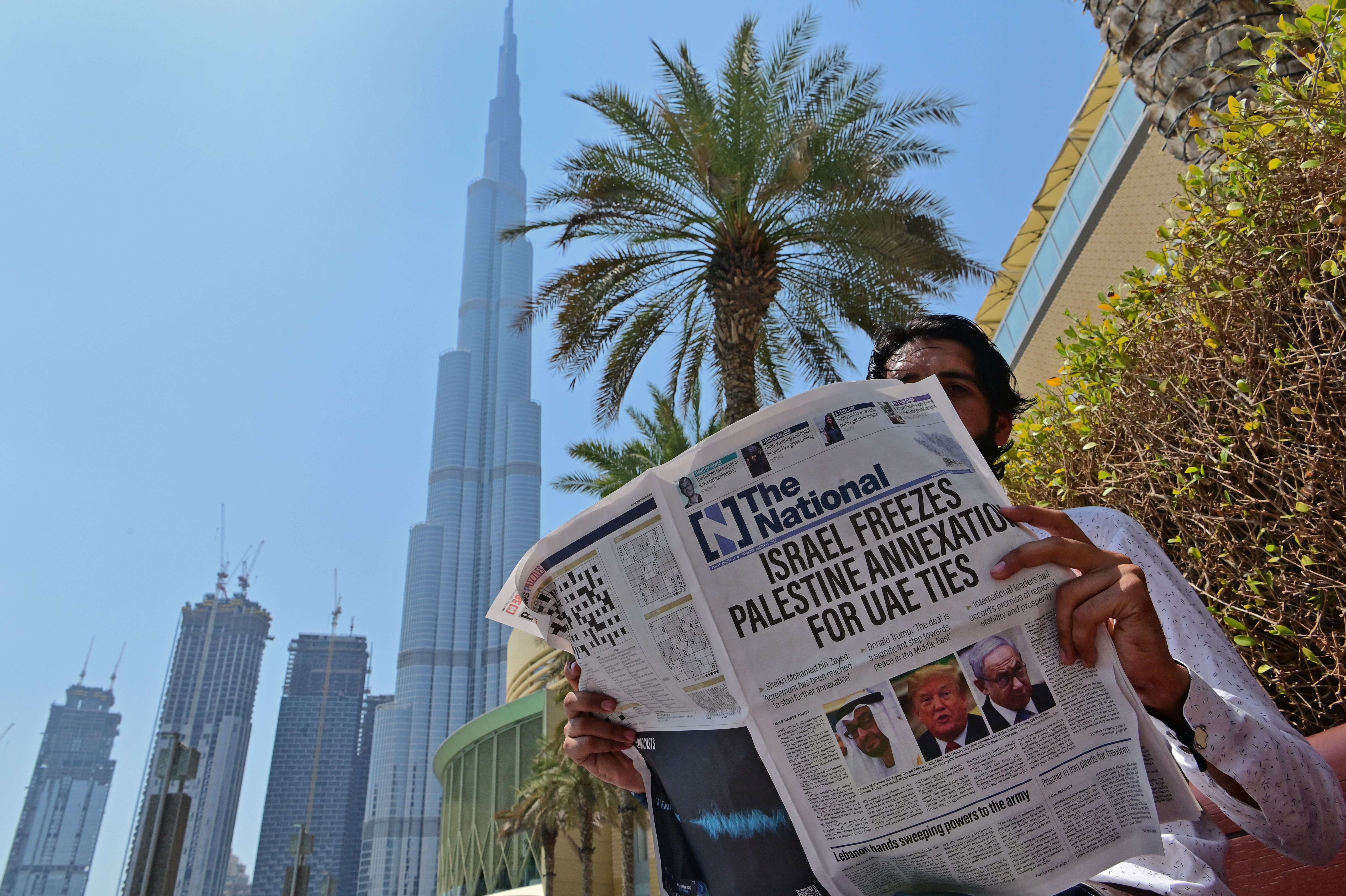 A man reads a copy of UAE-based The National newspaper near the Burj Khalifa, the tallest structure and building in the world since 2009, in the gulf emirate of Dubai on August 14, 2020, as the publication's headline reflects the previous day's news as Israel and the UAE agreed to normalise relations in a landmark US-brokered deal.
