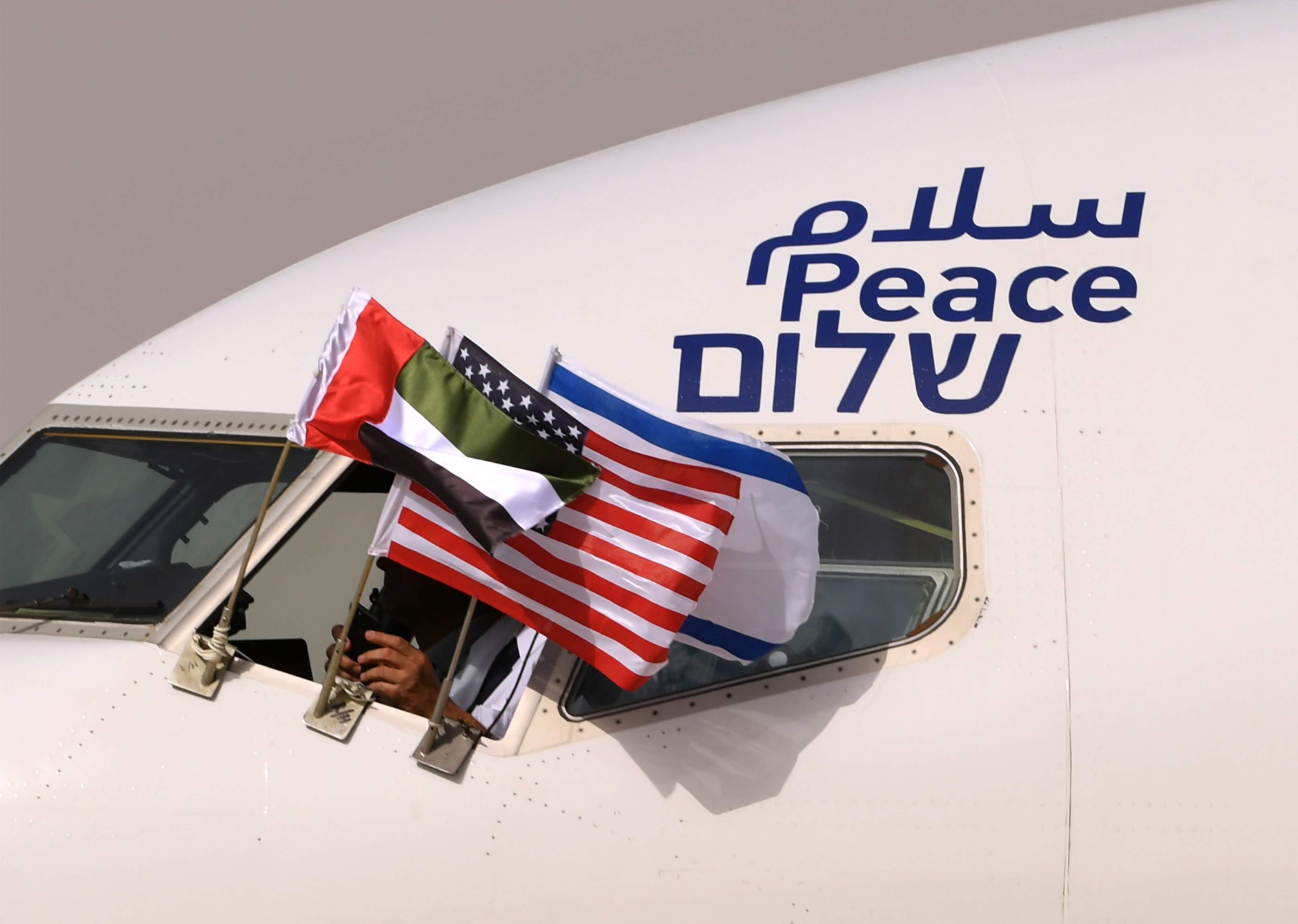 "The Emirati, Israeli and US flags are picture attached to an air-plane of Israel's El Al, adorned with the word ""peace"" in Arabic, English and Hebrew, upon it's arrival at the Abu Dhabi airport in the first-ever commercial flight from Israel to the UAE, on August 31, 2020."