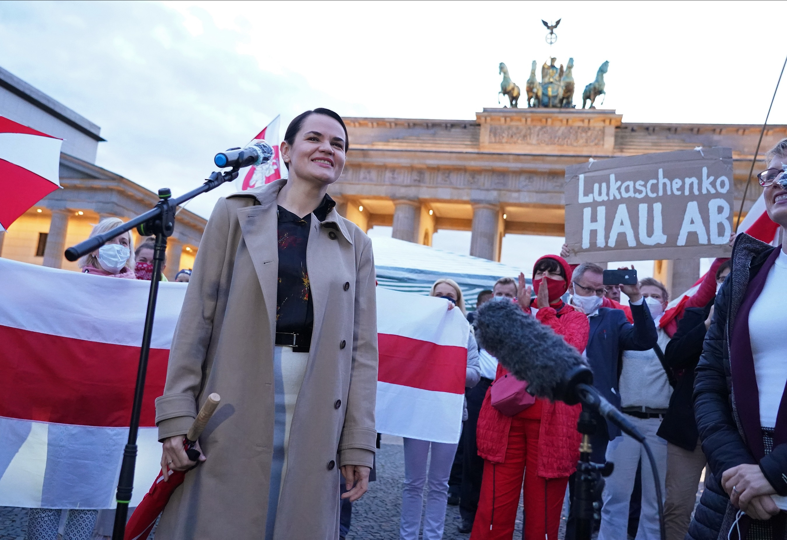 "Belarusian opposition leader Svetlana Tikhanovskaya arrives to speak to supporters, including one man holding up a sign that reads: ""Lukashenko go away!"" in reference to Belarusian President Alexander Lukashenko, at the Brandenburg Gate on October 05, 2020 in Berlin, Germany."