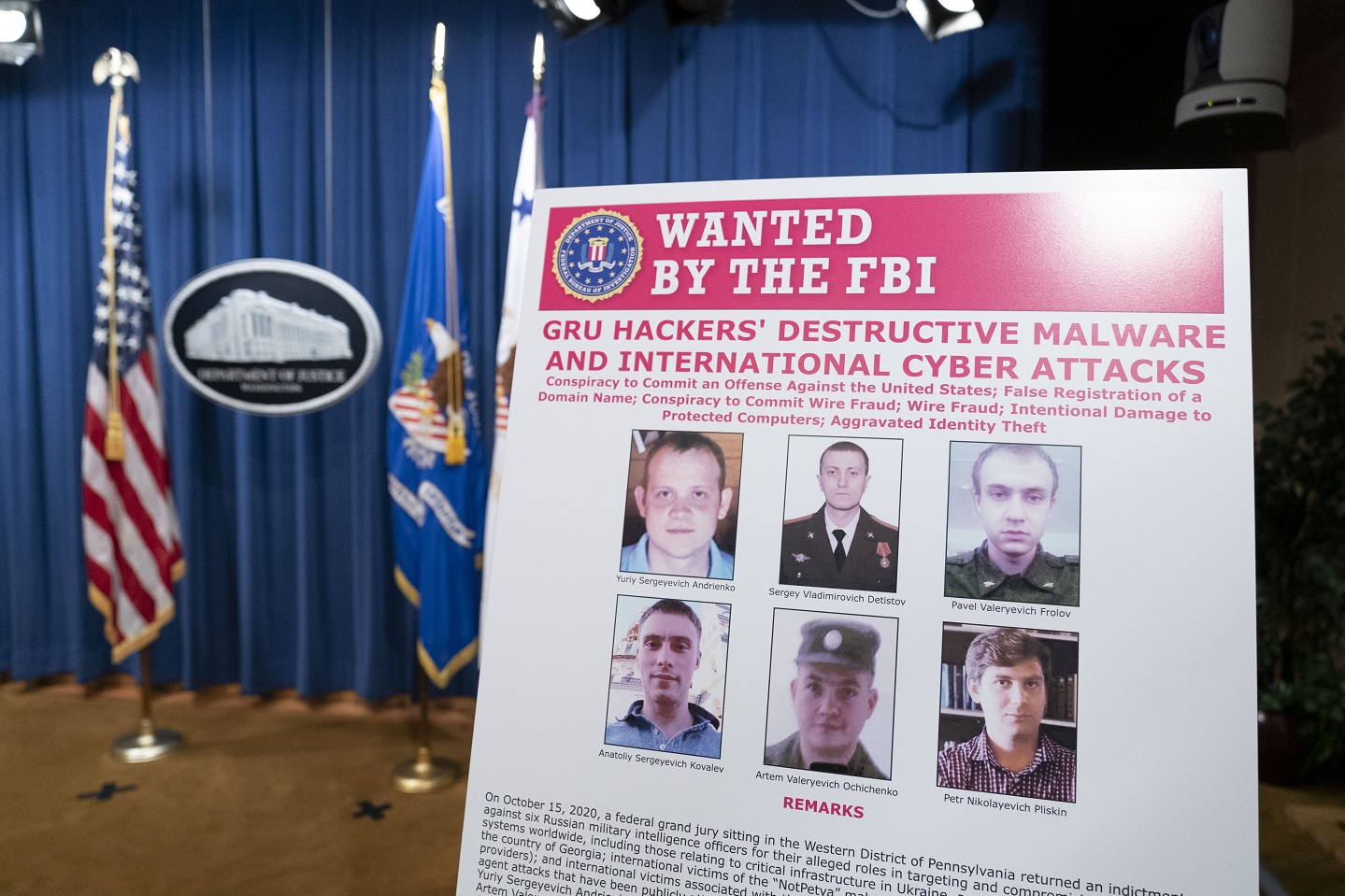 A poster showing six wanted Russian military intelligence officers is displayed before a news conference at the Department of Justice, on October 19, 2020 in Washington, DC.