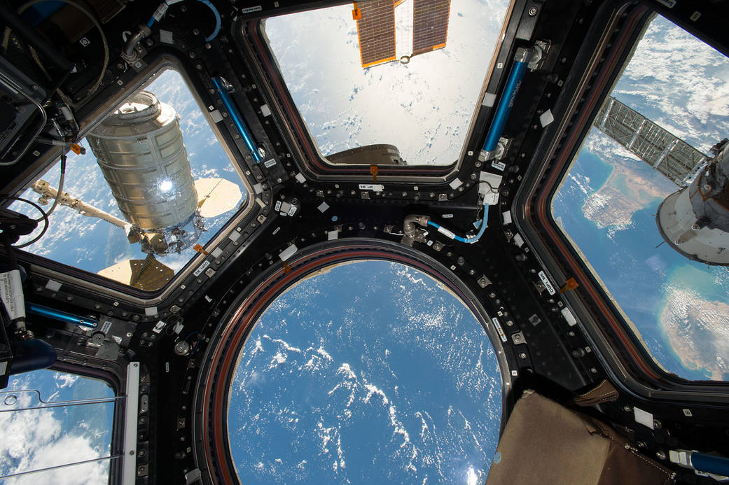 Orbital ATK's Cygnus cargo craft (left) is seen from the Cupola module windows aboard the International Space Station on Oct. 23, 2016. The main robotic work station for controlling the Canadarm2 robotic arm is located inside the Cupola and was used to capture Cygnus upon its arrival. The Expedition 49 crew will unload approximately 5,000 pounds of science investigations, food and supplies from the newly arrived spacecraft.