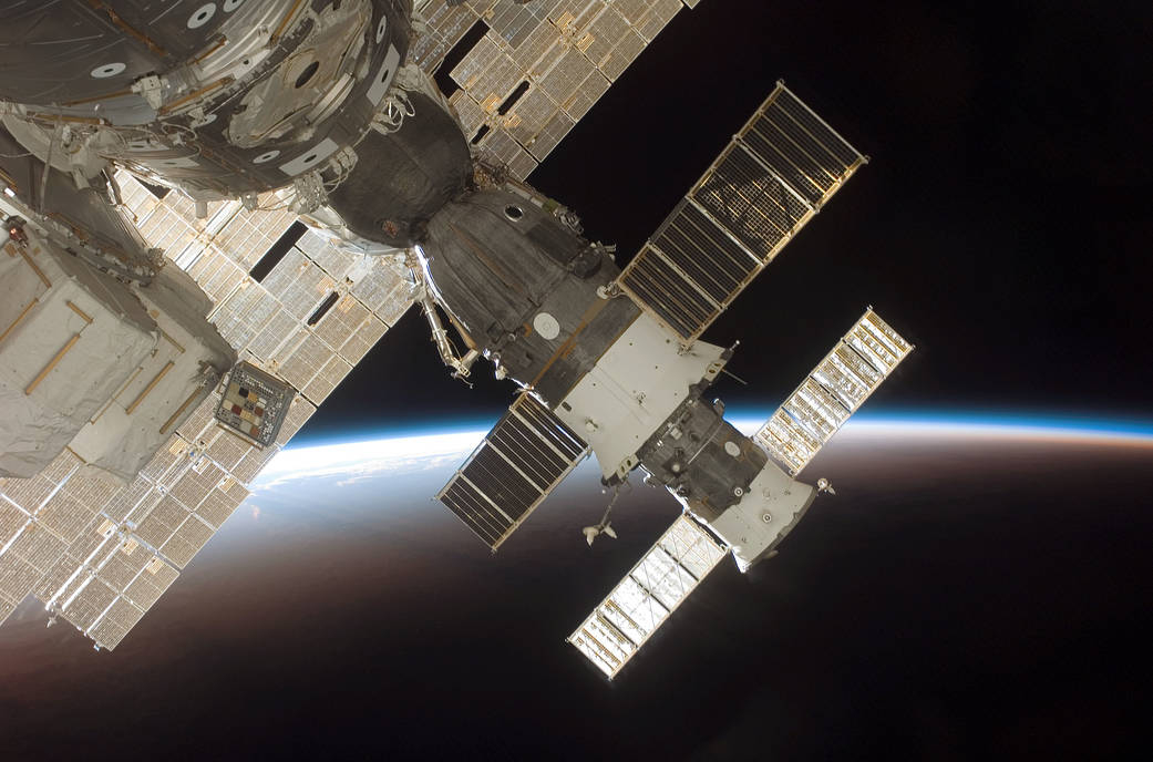 The blackness of space and Earth's horizon provide the backdrop for this image of the docked Soyuz 13 (TMA-9) (foreground) and Progress 22 resupply vehicle. The STS-116 crew protographed the Soyuz from a window on the International Space Station while Space Shuttle Discovery was docked with the station. NASA