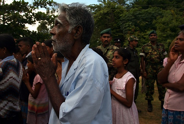 A man prays at a camp for the internally displaced due to fighting December 10, 2006 near the government controlled town of Kantalai in northeastern Sri Lanka. Some 5,000 Sinalese fled their villages in the past two days due to artillery attacks from the rebel Liberation Tamil Tigers of Eelam, (LTTE).