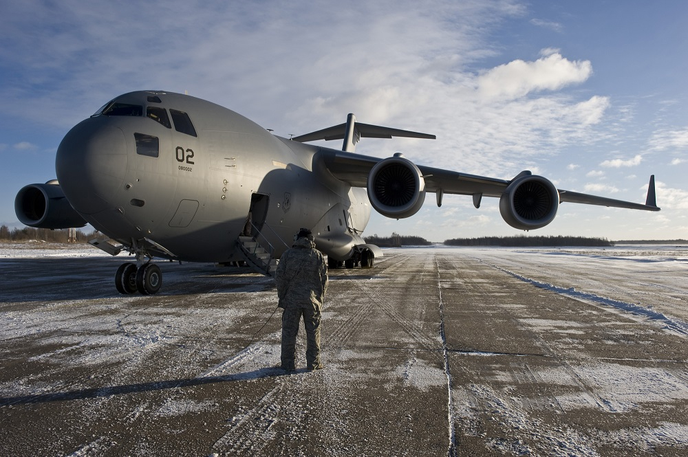 U.S. Air Force Tech. Sgt. Joseph Johns, a C-17 Globemaster III crew chief with the Heavy Airlift Squadron at Papa Air Base, Hungary, communicates with the C-17 pilots while on an airfield in Lithuania, Dec. 10, 2010. The aircraft was on the last leg of a three-day mission that would span over 7000 miles covering the countries of Hungary, Poland, Afghanistan and Lithuania as they move more than 75,000 tons of cargo.