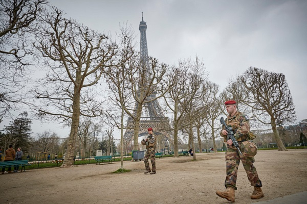 French army soldiers are walking in the park around the Eiffel Tower.