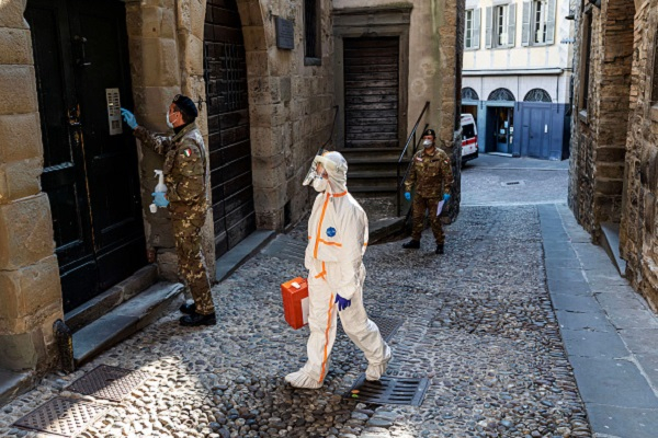 Two members of the military order of the Italian Red Cross escort in an alley of the old city, a member of the Italian Red Cross during his round of visits to the home of COVID-19 positive patients on April 6, 2020 in Bergamo, Italy.