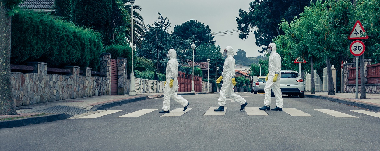 People in bacteriological protection suits walking down an empty street
