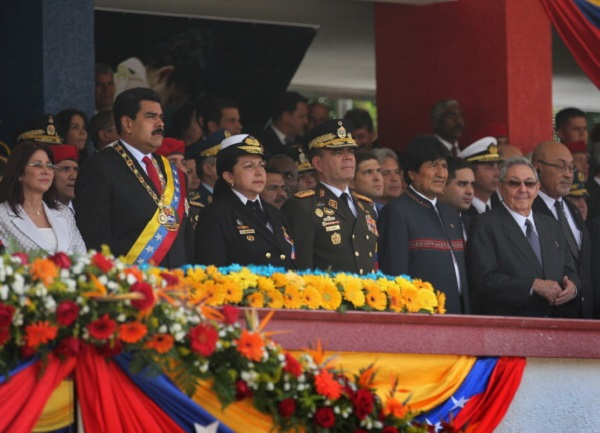 Venezuelan President Nicolas Maduro (L), stands with his military chiefs and honored guests Bolivian President Evo Morales (2nd R) and Cuban President Raul Castro (R) at an event marking the first anniversary of Hugo Chavez's death on March 5, 2014 in Caracas, Venezuela.