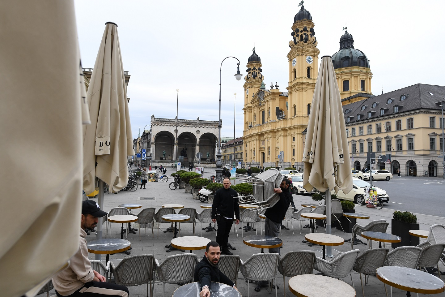 A photograph of employees at cafe Odeonsplatz removing chairs and tables from the terrace due to earlier closing hours on March 17, 2020 in Munich, Germany.
