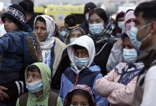 Migrants from the Moria camp in Lesbos island wearing masks to prevent the spread of the coronavirus, wait for a bus after their arrival at the port of Piraeus on May 4, 2020 in Athens, Greece.