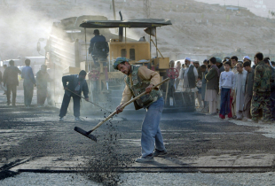 Afghan workers pave the road for a new traffic circle in Kabul, Afghanistan.