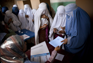 Afghan women in burqas vote at a polling station