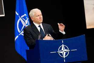 Photograph of then U.S. Secretary of Defense Robert Gates speaks at a Brussels defense conference in 2011 to persuade NATO members to finance the Alliance adequately or risk military decline.
