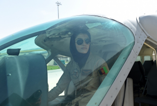 In a picture taken on April 26, 2015, Afghanistan's first female pilot Niloofar Rahmani, 23, sits in a fixed-wing Afghan Air Force aviator aircraft in Kabul. With a hint of swagger in her gait, Afghanistan's first female pilot since the ouster of the Taliban is defying death threats and archaic gender stereotypes to infiltrate an almost entirely male preserve.