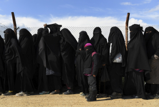 Wives and childern of former ISIS fighters line up in the foreign section of the al-Hawl refugee camp