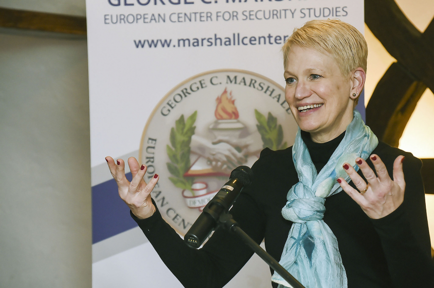 A femal participant speaking at the podium during the European security seminar.