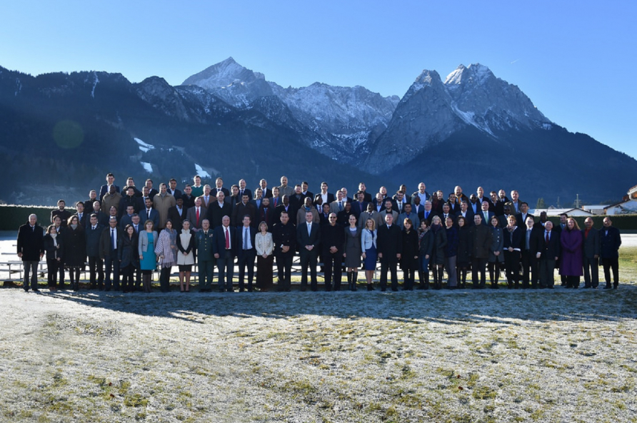 A photograph of students attending a PCSS course with the Zugspitze Mountain in the background.