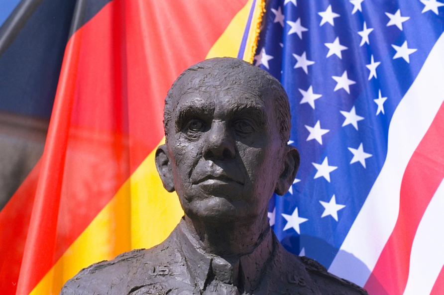 A photograph of the George C. Marshall statue with German and American flags in the background.