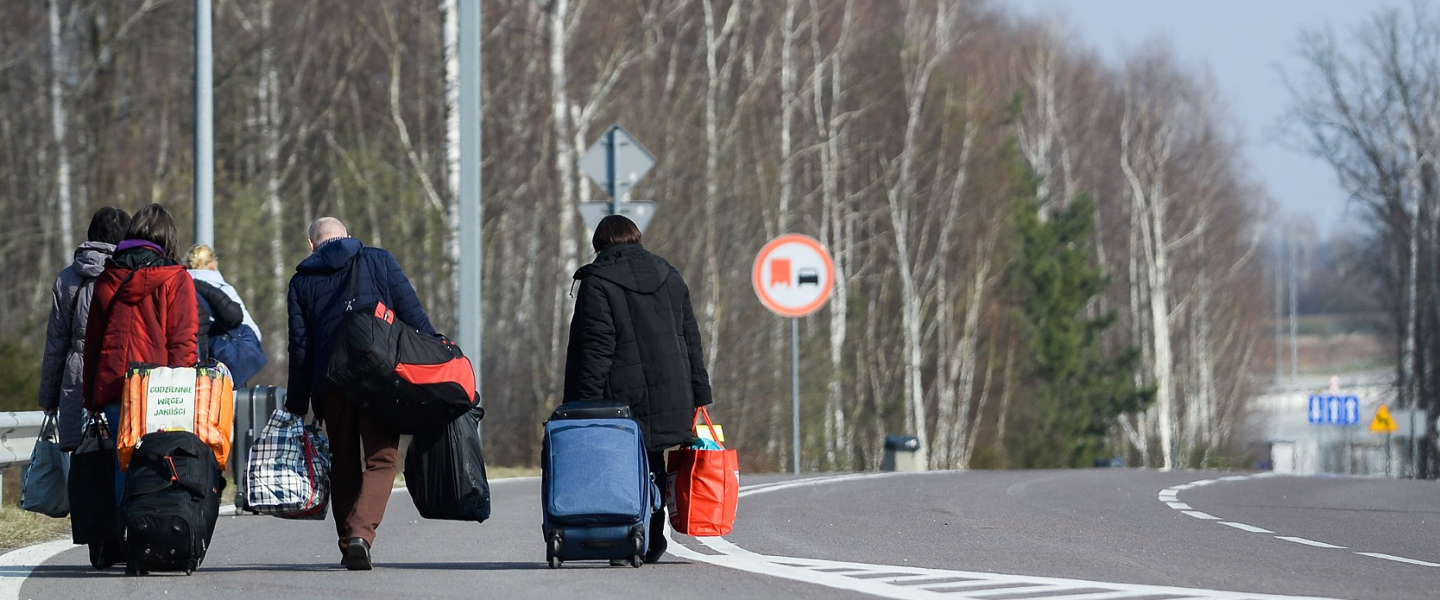 A photograph of  Ukrainian citizens carry their belongings as they walk towards a border check point to take an Ukrainian bus at the Polish-Ukrainian border Korczowa on March 28, 2020 in Korczowa, Poland.